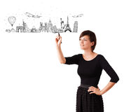 Young woman drawing famous cities and landmarks on whiteboard. Isolated on white Royalty Free Stock Photography