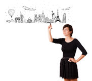 Young woman drawing famous cities and landmarks on whiteboard Stock Photography