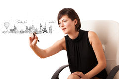 Young woman drawing famous cities and landmarks on whiteboard Stock Photos