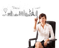 Young woman drawing famous cities and landmarks on whiteboard Stock Photo