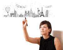 Young woman drawing famous cities and landmarks on whiteboard Royalty Free Stock Image