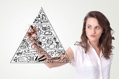 Young woman drawing a food pyramid on whiteboard. Young woman drawing a various food pyramid on whiteboard Royalty Free Stock Images