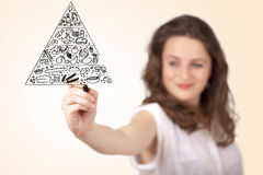Young woman drawing a food pyramid on whiteboard Stock Photo