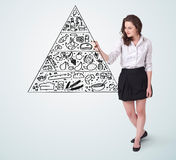 Young woman drawing a food pyramid on whiteboard Stock Images