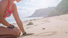 Young Woman Drawing Heart Shape in Sand on the Beach, Bali Stock Photo