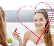 Young woman drawing heart to the mirror Stock Image