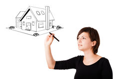 Young woman drawing a house on whiteboard Stock Photos