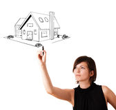 Young woman drawing a house on whiteboard Stock Photo