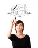 Young woman drawing a house on whiteboard Stock Image