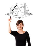Young woman drawing a house on whiteboard Royalty Free Stock Photos