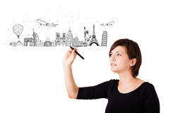 Young woman drawing landmarks on whiteboard. Young woman drawing famous cities and landmarks on whiteboard isolated on white Royalty Free Stock Photography