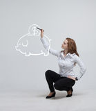 Young woman drawing a piggy Bank Royalty Free Stock Photography