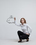 Young woman drawing a piggy Bank Royalty Free Stock Images