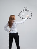 Young woman drawing a piggy Bank Royalty Free Stock Photos