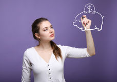 Young woman drawing a piggy Bank Stock Images