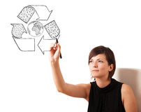 Young woman drawing recycle globe on whiteboard Stock Image
