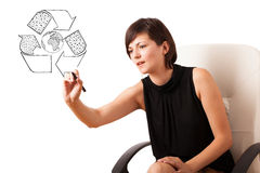 Young woman drawing recycle globe on whiteboard Stock Photo