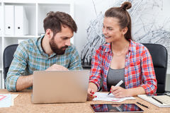 Young woman drawing schemes while man at computer watching Royalty Free Stock Images