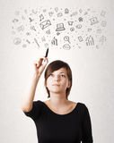 Young woman drawing and sketching icons and symbols Royalty Free Stock Images