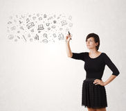 Young woman drawing and sketching icons and symbols Stock Photos
