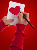 Young woman drawing valentine love heart Stock Photos