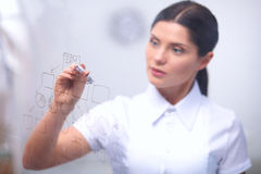 Young woman drawing on wihteboard with white Royalty Free Stock Photos