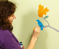 Young woman draws bird and flower on wall Stock Image