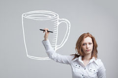 Young woman draws a Cup of coffee on grey Stock Photography