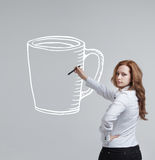 Young woman draws a Cup of coffee on grey Stock Photo