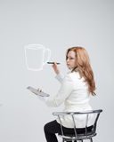 Young woman draws a Cup of coffee on grey Royalty Free Stock Photography
