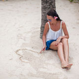 Young woman draws a heart in the sand with her Stock Images