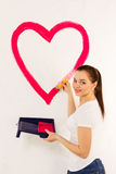 The young woman draws red paint heart Royalty Free Stock Photo