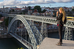 Young woman with dreadlocks takes pictures on the viewing platform opposite the Dom Luis I bridge across the Douro river in Porto Royalty Free Stock Image