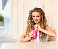 Young woman with dreads drinking beverage sitting outdoor in urban cafe. Cafe city lifestyle. Casual portrait of teenager girl. Stock Image