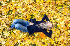 Young woman dreaming in autumn leaves Stock Photos