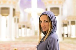 Young woman dreaming at the grand mosque of Sheikh Zayed Mosque in Abu Dhabi wearing abaya, paranja in night time. Travelling. Tra Royalty Free Stock Photos