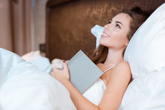 Young woman dreaming in her bed holding the book Royalty Free Stock Images