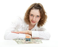 Young woman dreaming of her own house. Attractive young woman dreaming of her own house; young woman sitting at the table with small house model and dollar Stock Images
