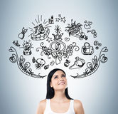 Young woman is dreaming about sopping. Shopping icons are flying in the air. Royalty Free Stock Photography