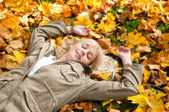 Young woman dreams in autumn leaves. Beautiful young blond woman dreams in autumn leaves royalty free stock photo