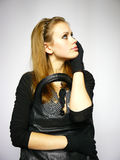 Young woman in a dress with black gloves. Woman in a dress with black gloves and a leather bag Stock Images