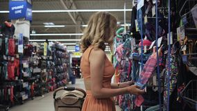 Young woman clothes in swimsuit in a shop in the sports department stock video