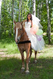Young woman in the dress of fiancee on a horse Stock Image