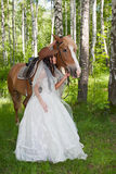 Young woman in the dress of fiancee next to a horse. By a canicular day in a birchwood royalty free stock photography