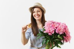 Young woman in dress, hat holding bitcoin, coin of golden color, bouquet of beautiful pink peonies flowers isolated on stock image