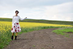 Young woman in dress hitchhiking near a canola field Royalty Free Stock Images