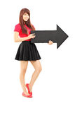 Young woman in dress holding a  arrow pointing to the right Stock Image