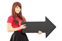 Young woman in dress holding a big black arrow pointing to the r Royalty Free Stock Images