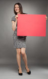 Young woman in dress  holding blank placard showing at it Royalty Free Stock Photo
