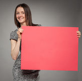 Young woman in dress  holding blank placard showing at it Royalty Free Stock Photography